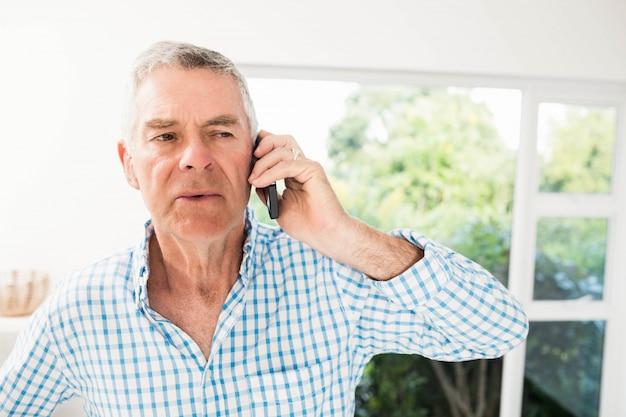 Senior homme sur un appel téléphonique dans la cuisine