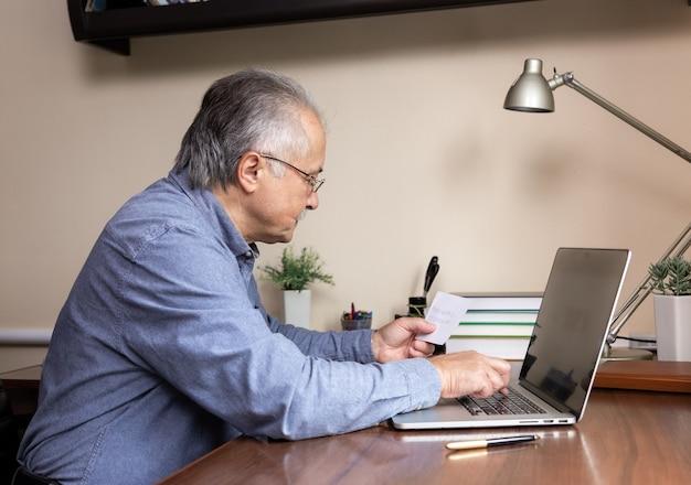 Senior homme apprend à utiliser l'ordinateur. vieil homme en verre et chemise bleue entre un mot de passe à partir d'un morceau de papier. concept à l'aide d'un ordinateur portable pour étudier en ligne au bureau à domicile