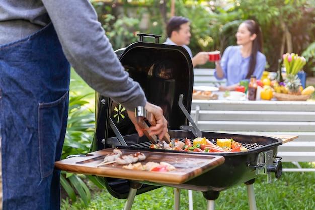 Senior homme asiatique portant un tablier et ayant un barbecue dans le parc.