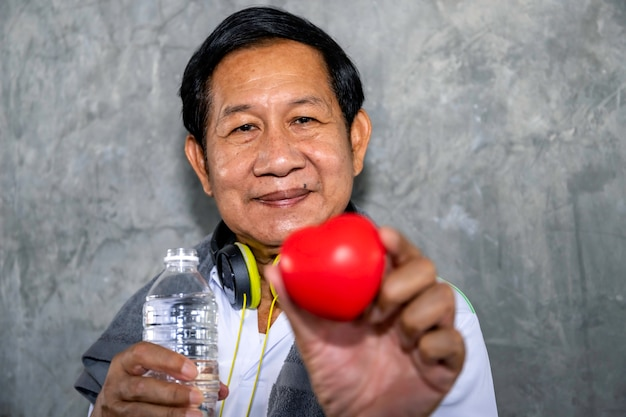 Senior homme asiatique souriant en tenue de sport tenant coeur rouge. bonne vie.