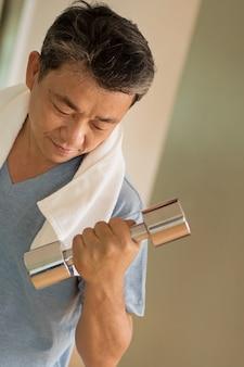 Senior homme asiatique travaillant, musculation avec haltère