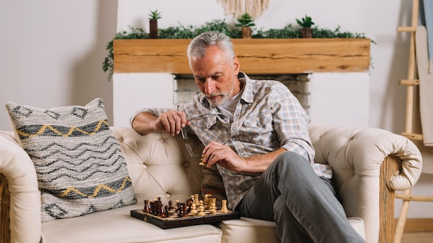 Senior homme assis sur un canapé jouant aux échecs à la maison