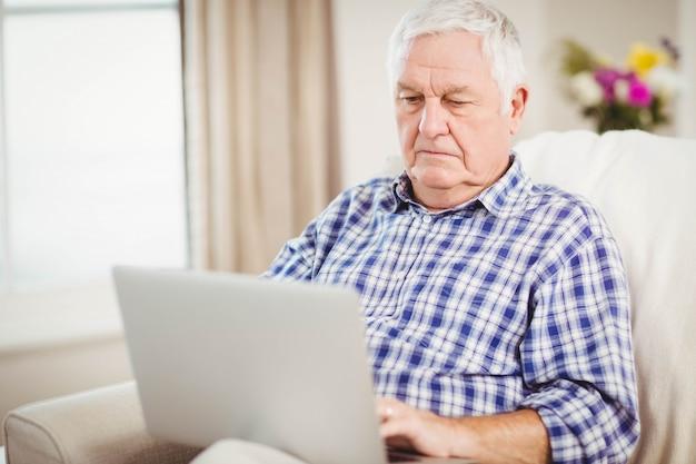 Senior homme assis sur un canapé et utilisant un ordinateur portable dans le salon