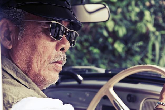 Senior homme assis dans sa voiture