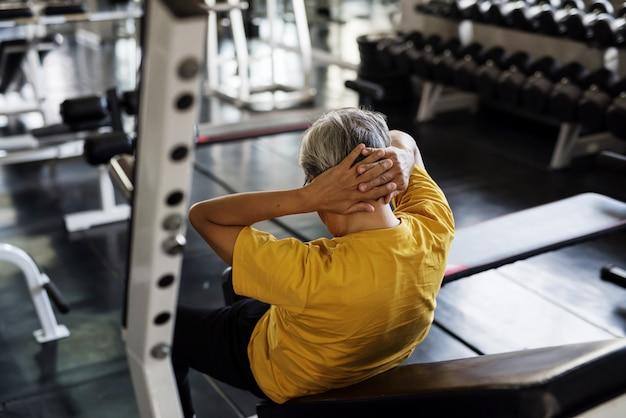 Senior homme assis dans la salle de gym