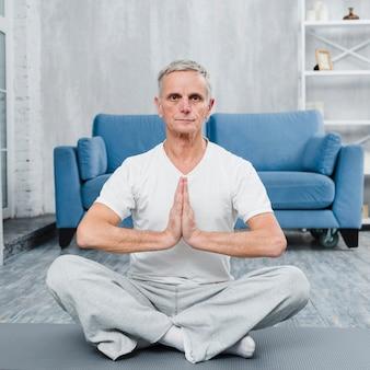 Senior homme assis sur un tapis de yoga fait un geste de prière