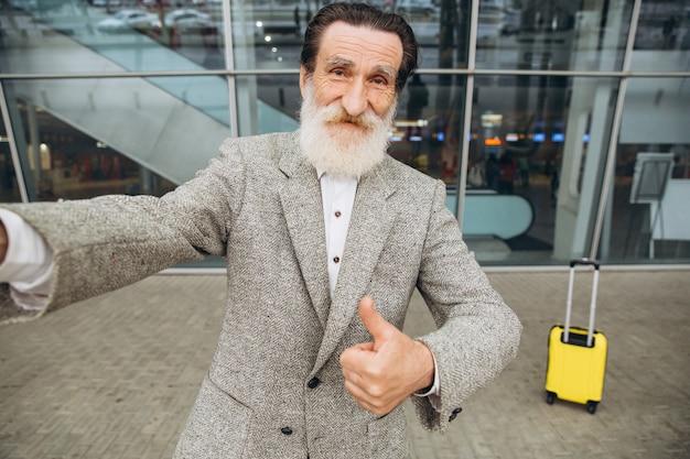 Senior homme à barbe grise avec valise de transport jaune et plan de la ville faire selfie sur l'arrière-plan du bâtiment de l'aéroport.