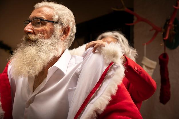 Senior homme à la barbe s'habillant en père noël