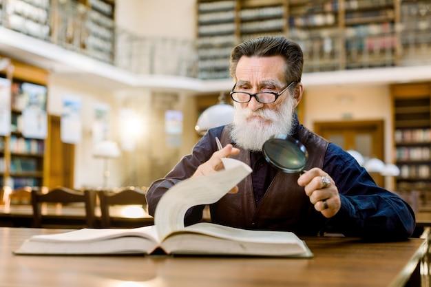 Senior homme barbu dans des verres et chemise élégante et gilet en cuir assis à la table dans la bibliothèque vintage, tenant une loupe