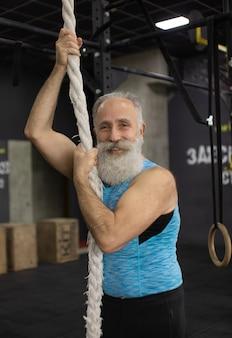 Senior homme barbu exerçant avec des cordes au gymnase. activité physique et mode de vie sain.