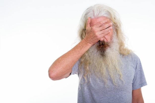 Senior homme barbu à la fatigue tout en couvrant les yeux