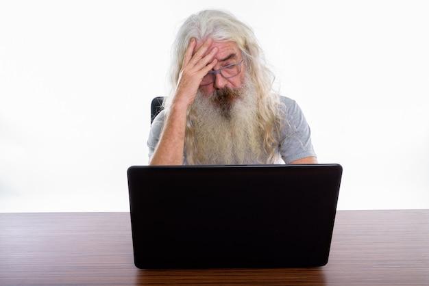 Senior homme barbu portant des lunettes tout en utilisant un ordinateur portable