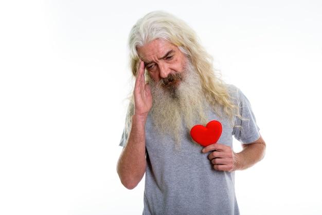 Senior homme barbu tenant un coeur rouge tout en ayant des maux de tête