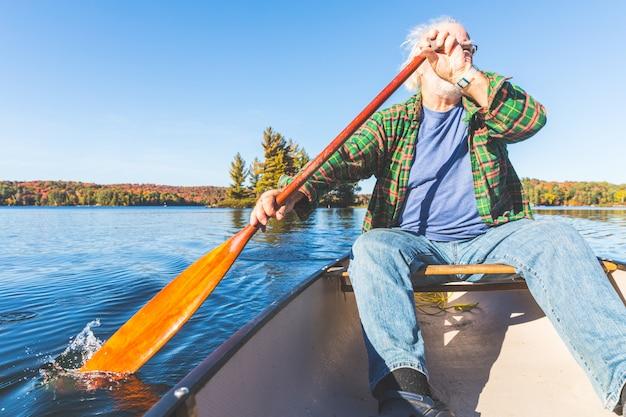 Senior homme avec canoë ramer sur une journée ensoleillée