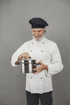 Senior homme avec casserole en métal. chef dans un chapeau noir. approche professionnelle des affaires.