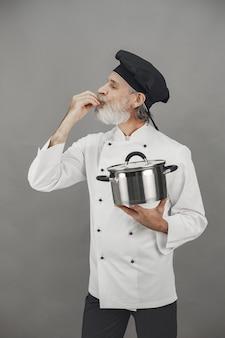 Senior homme avec casserole en métal. chef dans un chapeau noir.