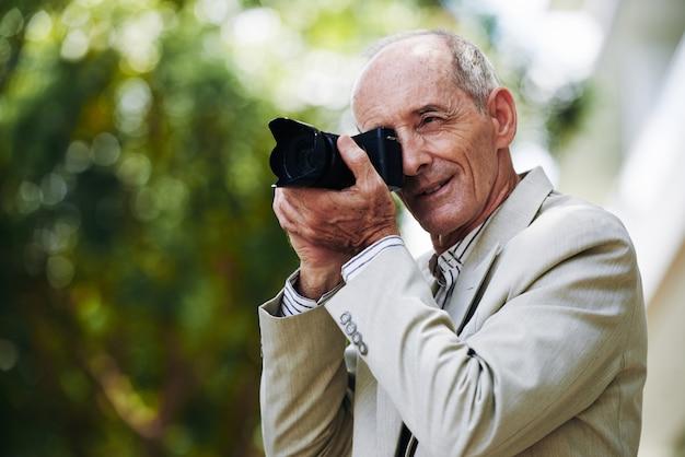 Senior homme caucasien en costume prenant des photos dans la rue