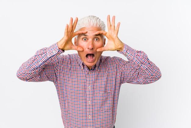 Senior homme caucasien isolé en gardant les yeux ouverts pour trouver une opportunité de réussite.