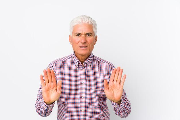 Senior homme caucasien isolé rejetant quelqu'un montrant un geste de dégoût.