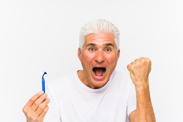 Senior homme caucasien tenant une lame de rasoir isolé acclamant sans soucis et excité. concept de victoire.