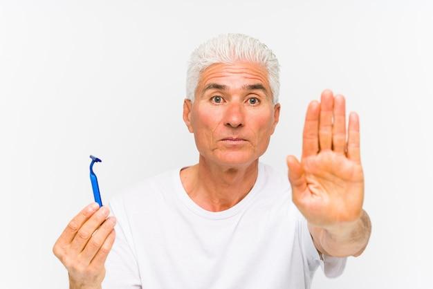 Senior homme caucasien tenant une lame de rasoir isolé debout avec la main tendue montrant le panneau d'arrêt, vous empêchant.