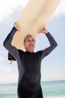 Senior homme en combinaison en cours d'exécution avec planche de surf sur la tête