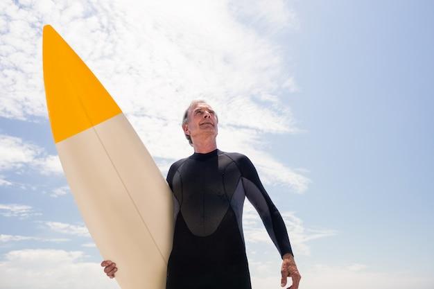 Senior homme en combinaison de surf tenant une planche de surf