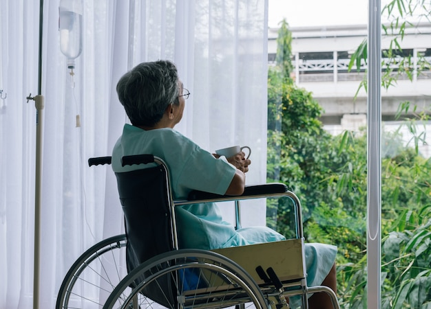Senior homme dans un fauteuil roulant seul dans une pièce regardant par la fenêtre de l'hôpital