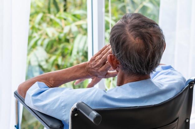 Senior homme dans son fauteuil roulant avec le dos à l'hôpital.