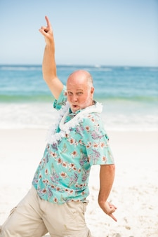 Senior homme dansant sur la plage
