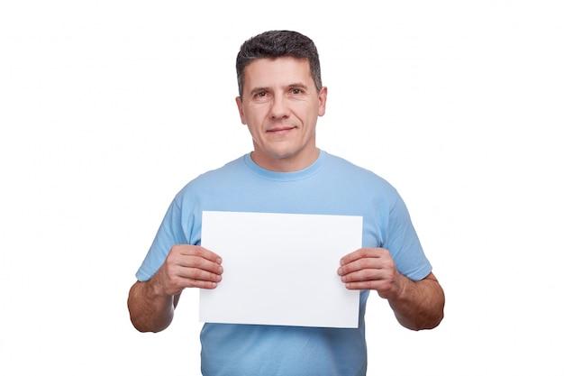 Senior homme détient une feuille de papier vierge à deux mains et souriant.
