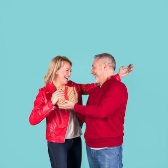 Senior homme donnant une boîte cadeau à sa femme blonde mature gaie