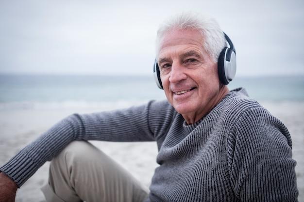 Senior homme écoutant de la musique sur des écouteurs