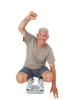 Senior homme encourageant l'échelle de poids
