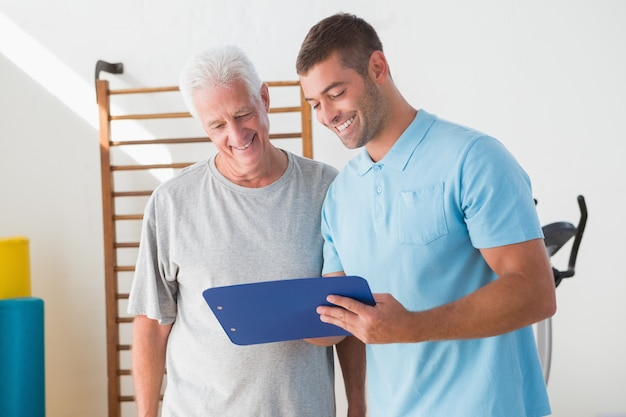 Senior homme avec entraîneur en regardant le presse-papiers