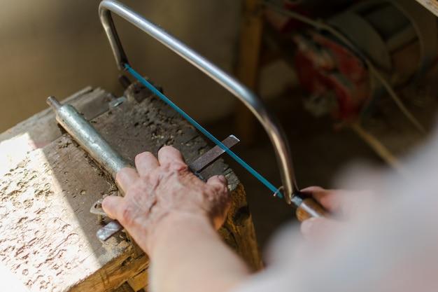 Senior homme essayant de couper le fer avec une scie à métaux