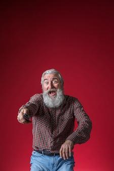 Senior homme excité devant la télévision assis sur un fond rouge
