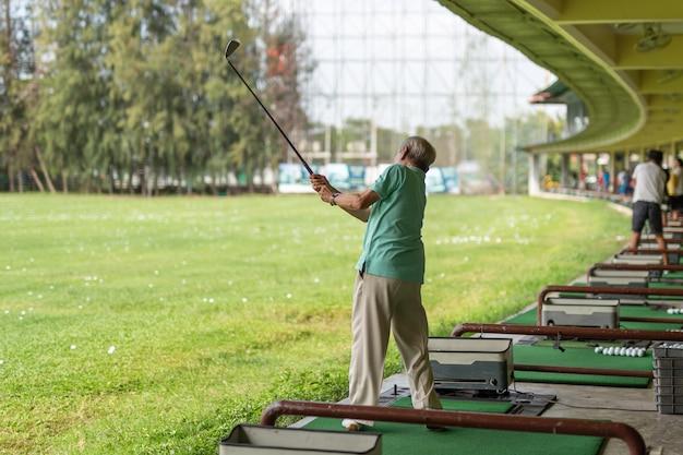 Senior homme exerce son swing au practice de golf.
