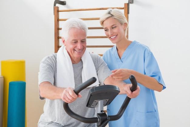 Senior homme, faire du vélo d'appartement avec un thérapeute