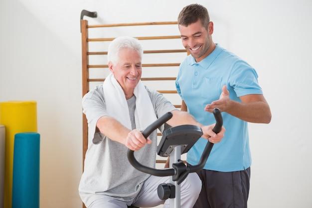 Senior homme, faire du vélo d'exercice avec son entraîneur
