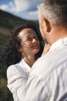 Senior homme et femme dans les montagnes. couple adulte amoureux au coucher du soleil. homme en chemise blanche.