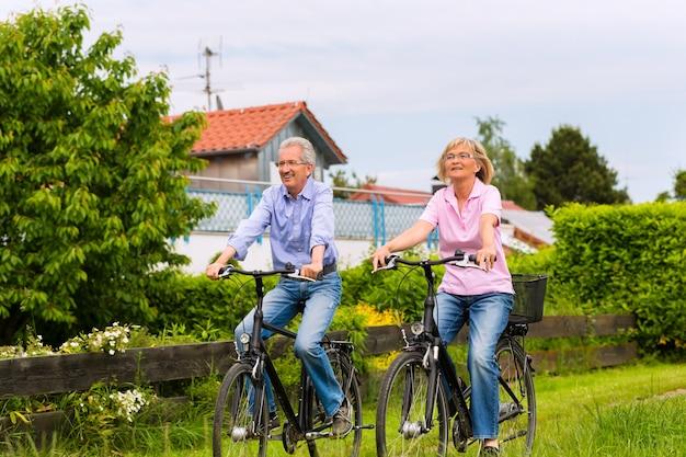 Senior homme et femme exerçant avec des vélos à l'extérieur, ils sont un couple