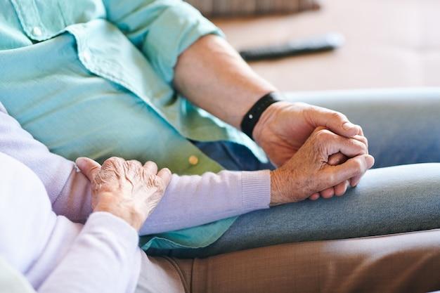 Senior homme et femme en tenue décontractée tenant par la main tout en passant du temps ensemble à loisir ou week-end
