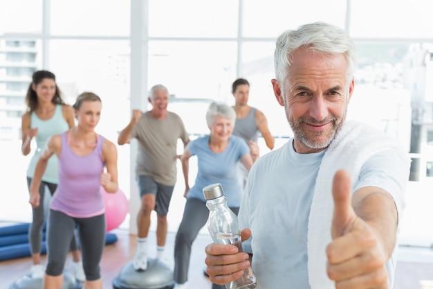 Senior homme gesticulant pouce en l'air avec des personnes exerçant dans un studio de remise en forme