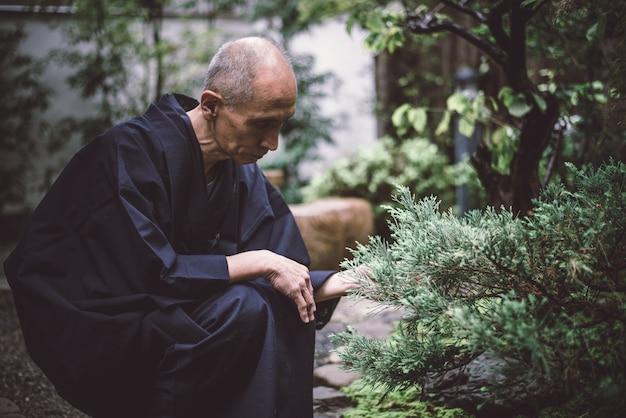 Senior homme japonais en prenant soin de son jardin