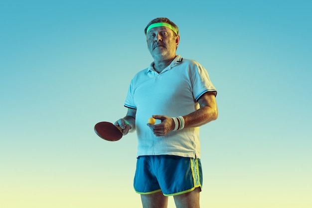 Senior homme jouant au tennis de table sur un mur dégradé en néon. le modèle masculin de race blanche en grande forme reste actif, sportif. concept de sport, activité, mouvement, bien-être, mode de vie sain.
