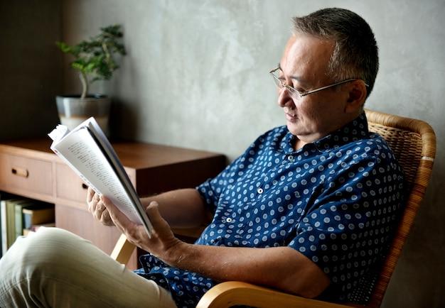 Senior homme lisant un livre à la maison