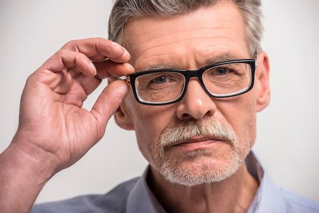 Senior homme à lunettes sur gris