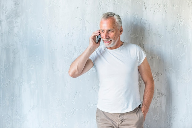 Senior homme avec les mains dans la poche, parler sur téléphone portable