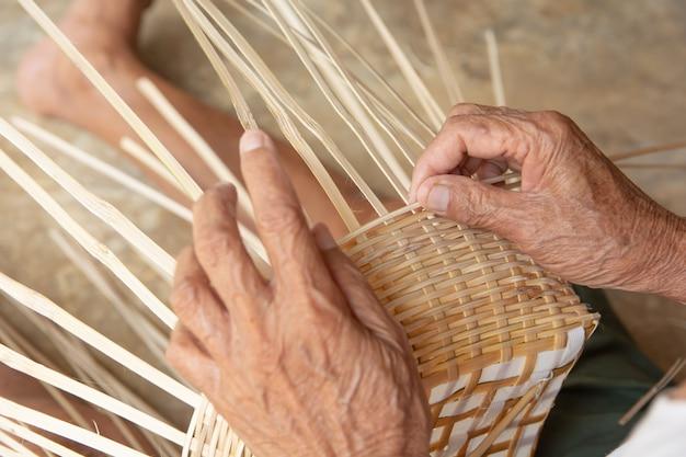 Senior homme mains tissant manuellement le bambou.